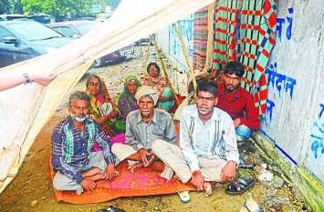 बारिश में तिरपाल तानकर धरने पर बैठे आदिवासी, उधर अतिक्रमण का दौर जारी