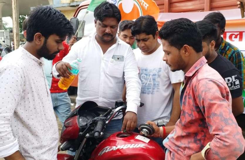 चम्मच से गाड़ी में पेट्रोल डालकर जता रहे महंगाई का विरोध