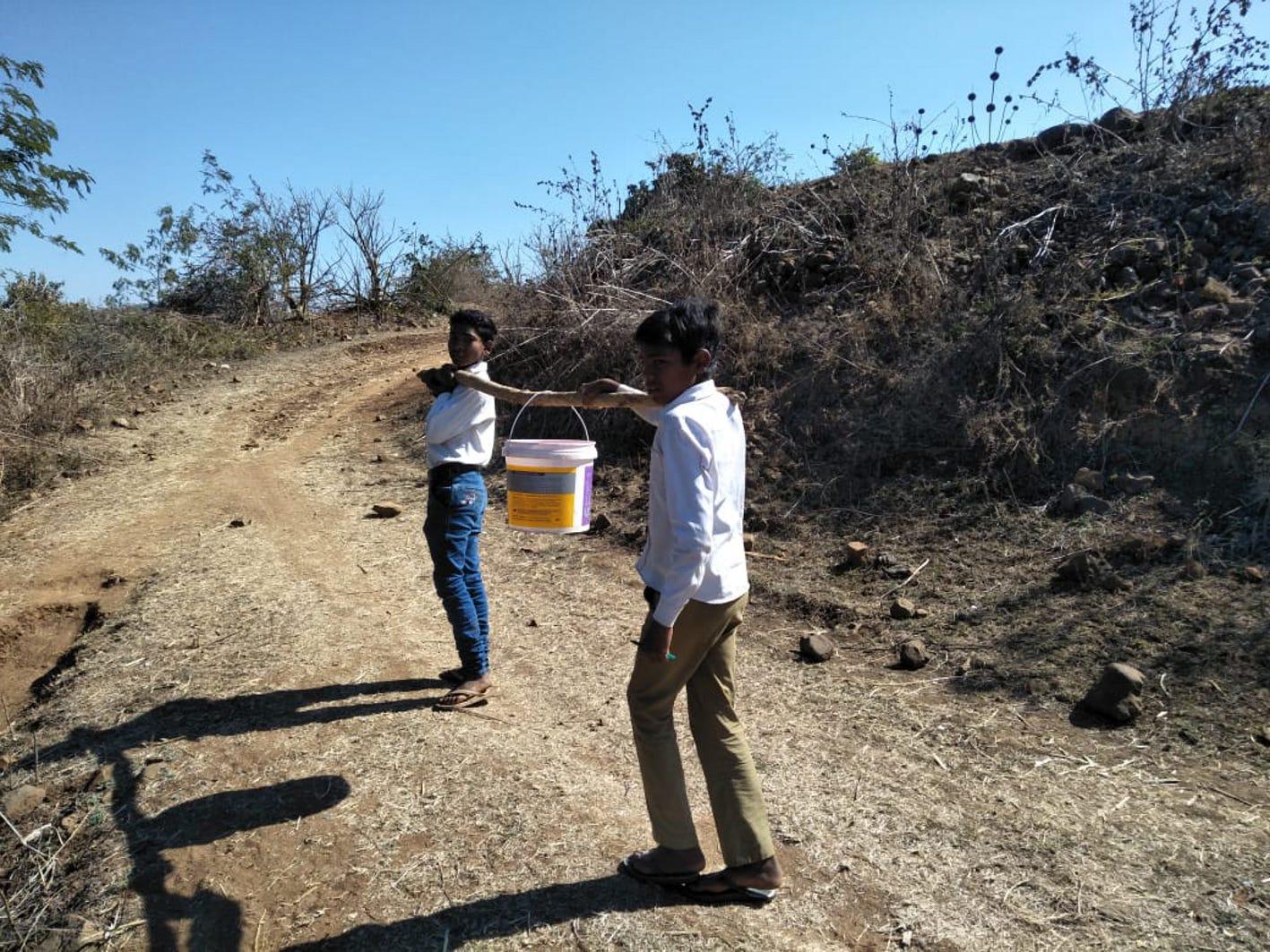 पानी की बाल्टी लेकर ऊबड़-खाबड़ पहाड़ी में चढ़ते हैं स्कूली बच्चे