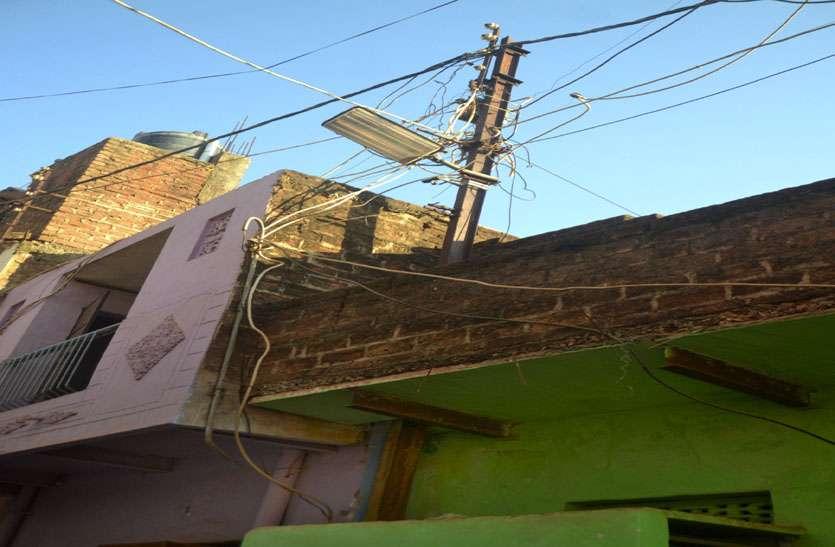 कंपनी ने नहीं हटाए तो मकानों में ही चुनवा लिए बिजली के खंभे, अब रोज छज्जों पर करंट का डर