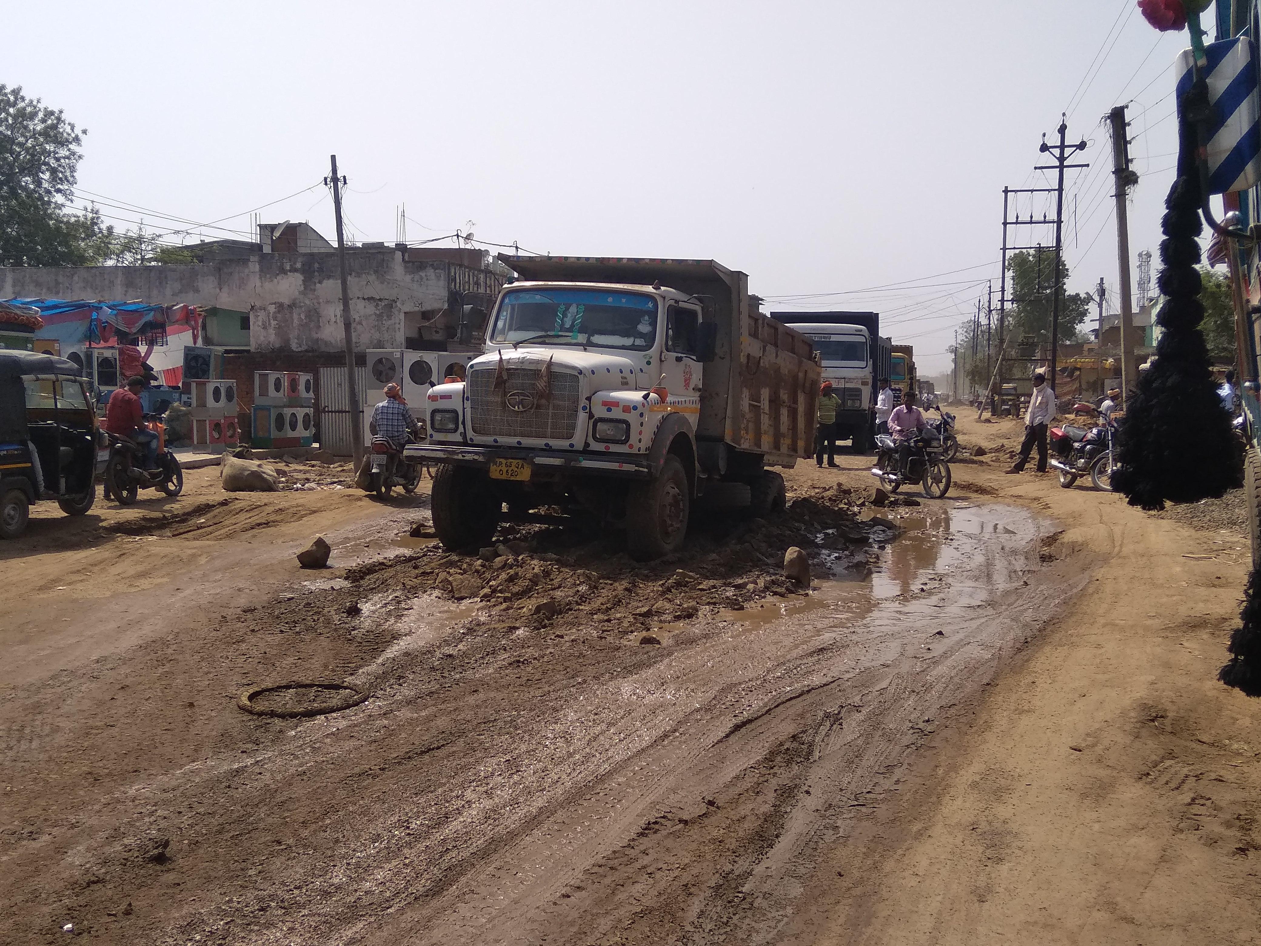 कीचड़ में फंसा बोल्डर से लदा ट्रक, आधा घंटा यातायात हुआ प्रभावित