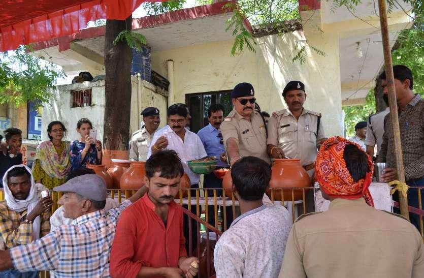तस्वीरों में देखें पुलिस ने गुड़-चना बाटकर तर कराया राहगीरों का गला
