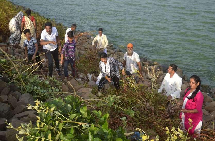 तालाब की पार पर आड़े-तिरछे पत्थरों पर खड़े होकर कर रहे श्रमदान