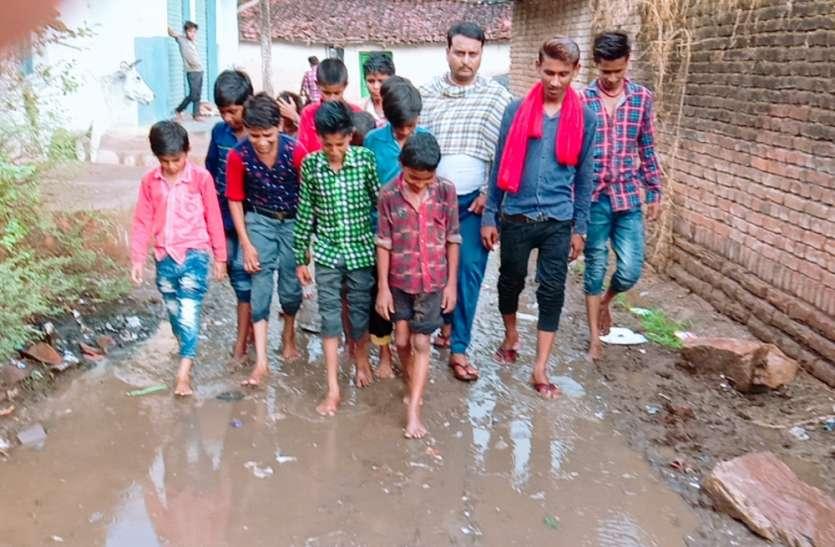 बारिश में घुटनों तक कीचड़ से सनी सड़क से स्कूल जाते हैं बच्चे