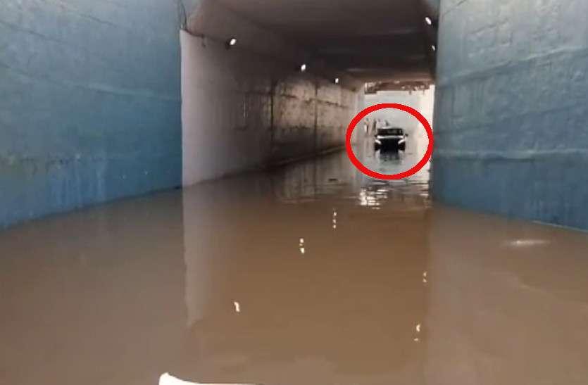 VIDEO: लबालब पानी से भरे अंडरब्रिज में फंसी कार, इधर धसक रही दीवार...