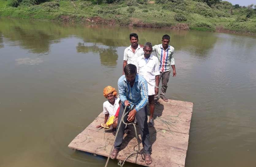 जान जोखिम में डाल चार ड्रम के सहारे कर रहे सैंकड़ों ग्रामीण नदी पार