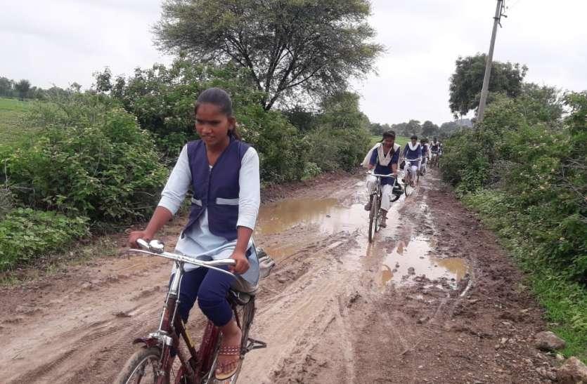 कीचड़ भरे मार्ग से सायकल चलाकर स्कूल जाने को मजबूर छात्राएं