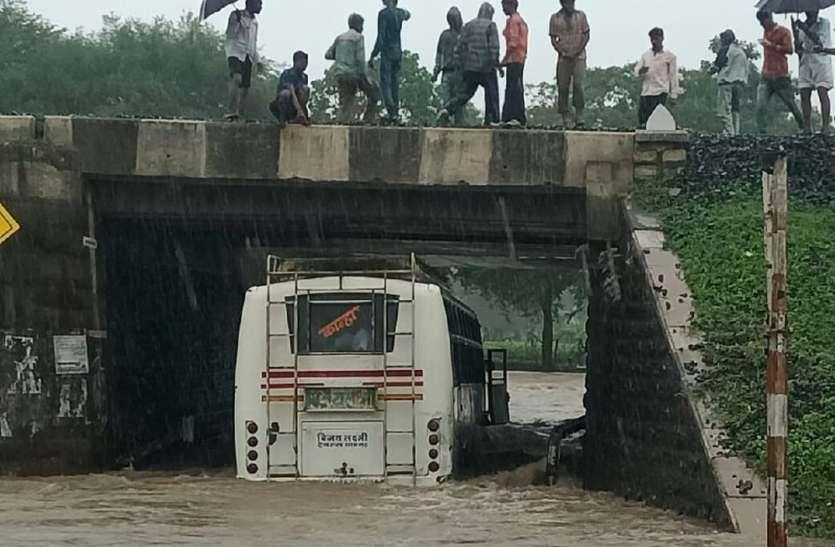 अंडरब्रिज के पानी में फंसी बस, काच फोड़कर यात्रियों को निकाला को लोगों ने बचाया