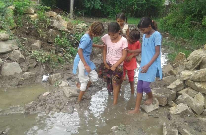 घुटने-घुटने कीचड़ से होकर स्कूल जा रही बालिकाएं