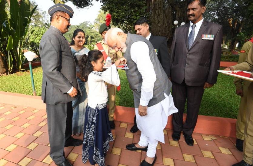 सशस्त्र बल झंडा दिवस के मौके पर छोटी बच्ची ने PM मोदी की जैकेट में लगाया झंडा