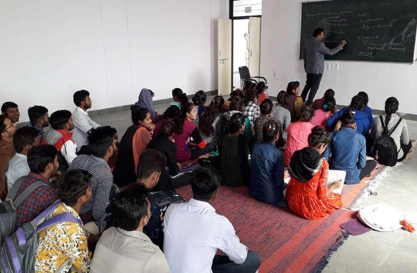फर्श पर बैठ कर पढ़ रहे हैं कॉलेज के छात्र