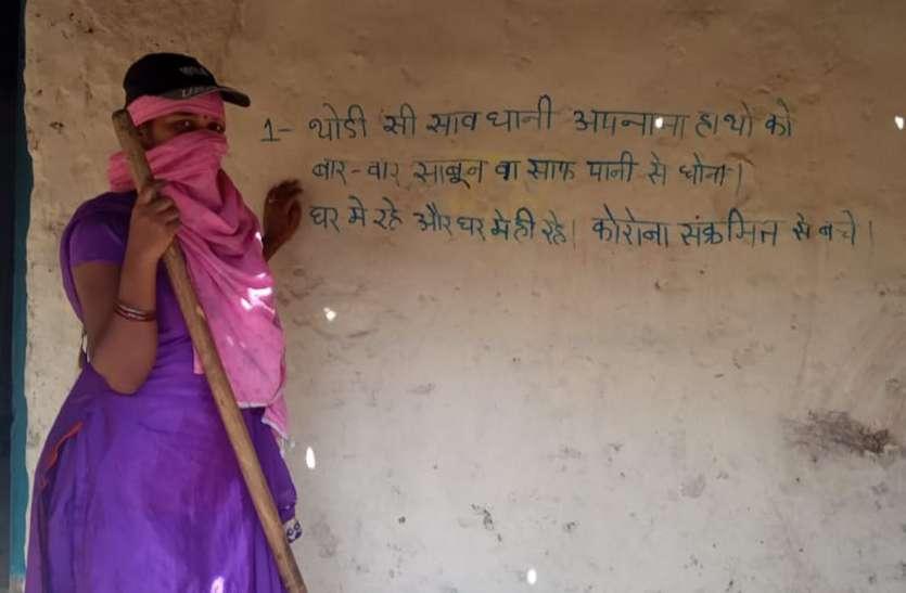 विकलांग महिला घर की दीवारों में कोरोना से बचने का लिख रही नारा