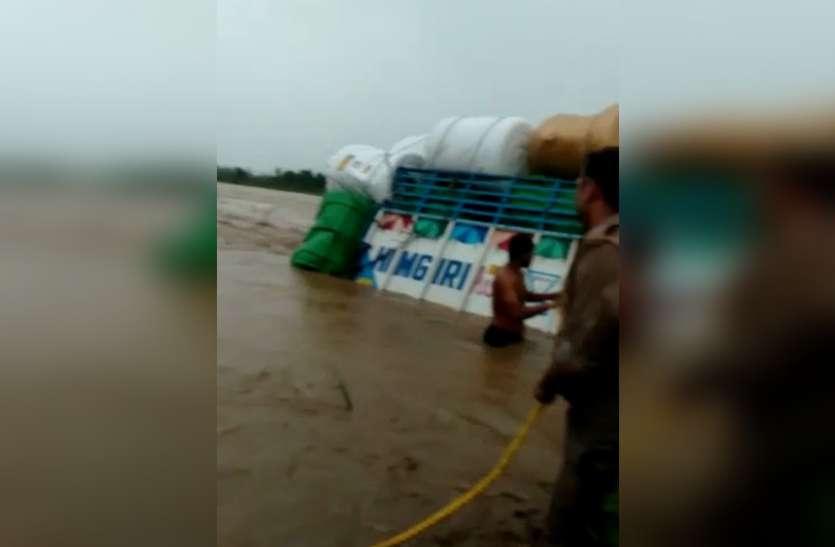 बारिश से अचानक बढ़ा नदी का जलस्तर, वाहन समेत पति-पत्नी तेज बहाव में बहे, पुलिसकर्मियों ने बचाई जान