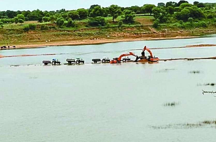 केन नदी के  रामपुर घाट में हैवी मशीन से निकाल रहे रेत
