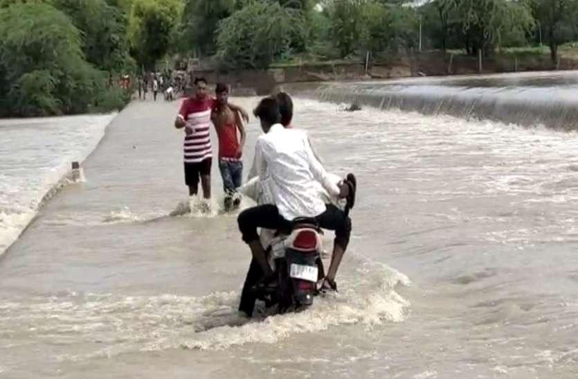 खतरे में डाल रहे जान, बहते पानी को पार कर रहे लोग