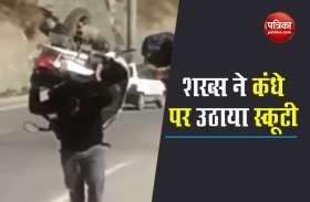 VIDEO: स्कूटी को कंधे पर उठाकर चलने लगा शख्स, देख कर लोग रह गए अचंभित
