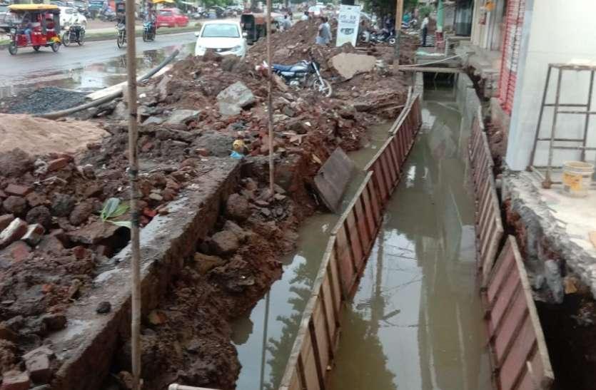 बारिश में बन रही नाली, सड़क पर फैली निर्माण सामग्री