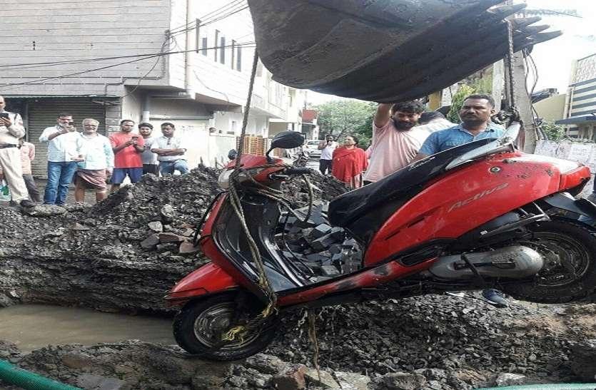 अपनी गाड़ी सहित सड़क पर बने 6 फीट गहरे गड्ढे में जा गिरा वाहन चालक, जेसीबी से निकाली गाड़ी