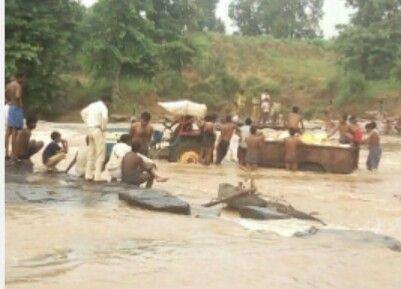 राशन लदा ट्रैक्टर टूटे पुल में फंसा, लोगों ने कूदकर बचाई जान